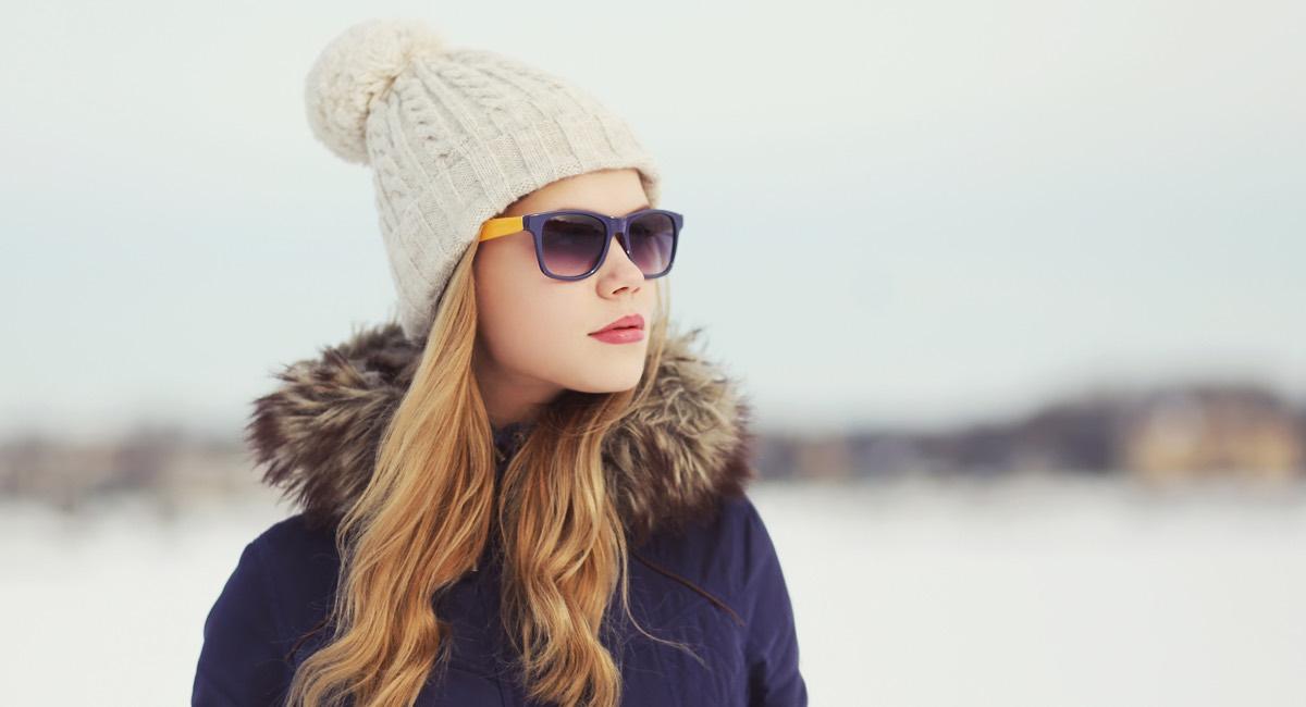 Ung kvinne med solbriller i snø og minusgrader